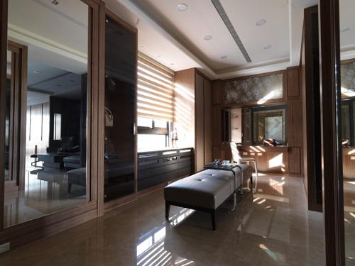 主臥更衣間設有大面全身鏡、透明展示櫃、化妝區,以及特別規劃在中間的休憩區,是母女交換穿衣意見的溫馨設計。
