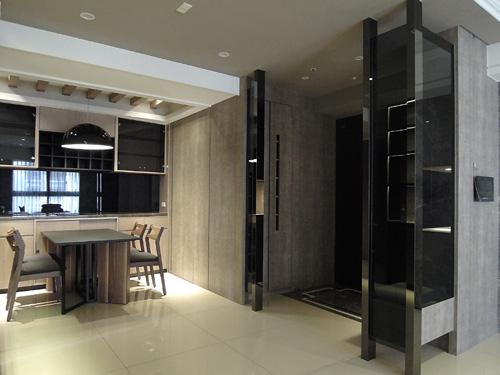 以黑灰鈦金玻璃與木質櫃體組成的玄關空間,融合了鞋子與玄關小物的收納功能,寬敞且機能完整。