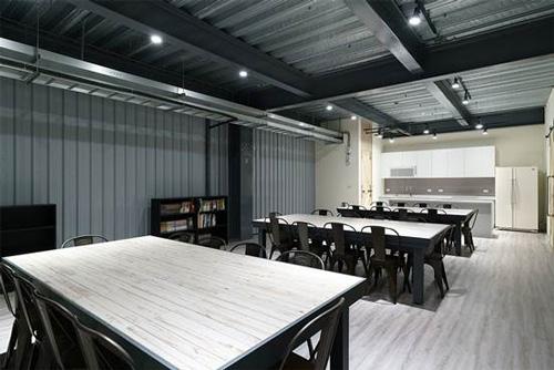 員工餐廳用木紋塑膠地板、木紋磚餐桌,搭配白色廚具,營造簡約俐落空間。